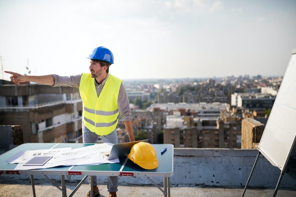 Young man architect, construction engineer at a construction site